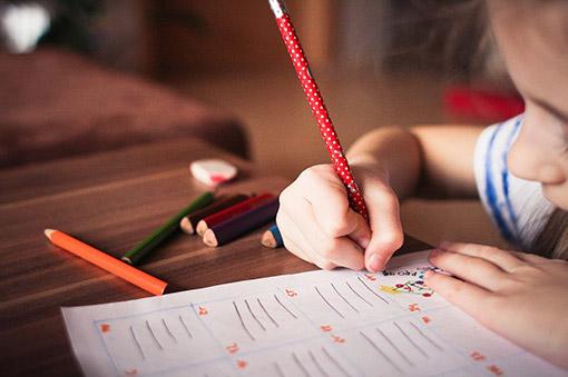 Ein Mädchen sitzt an ihreren hausaufgaben während sie ein Bild malt